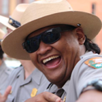 A young male ranger laughs while pointing at the camera