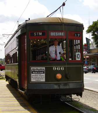 A man driving a green trolley smiling as he poses for a picture with the trolley