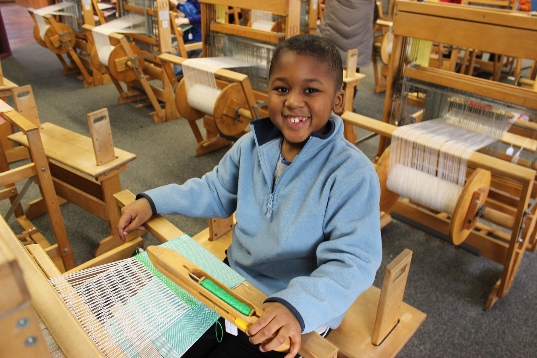 A boy weaving at the Tsongas Industrial History Center