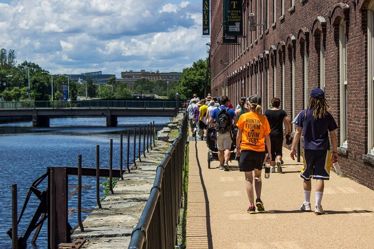 A group of visitors hiking along the Northern Canal and Suffolk Mill during an Urban Hike.