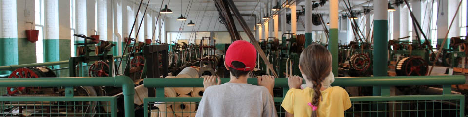 Boott Mills weave room with two children watching the looms from behind a railing