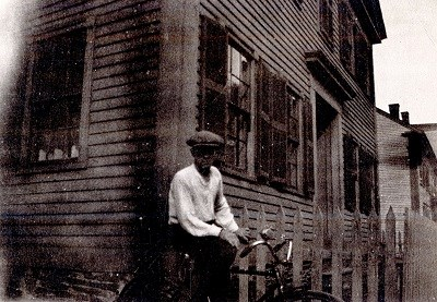 "A man poses on a bicycle in the historic ""Acre"" neighborhood"