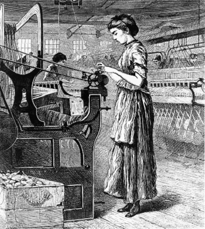 A weaver stands at a loom on a factory floor