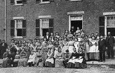 A long brick boardinghouse with workers posed outside