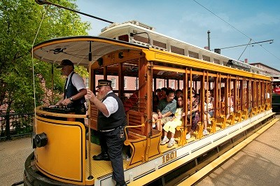 A green and yellow trolley full of visitors travels past a historic mill building