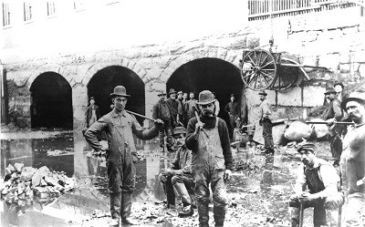 A historic image of a group of canal workers posing with their tools in the Merrimack Canal
