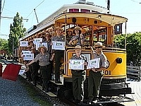 Rangers on a trolley with NPS Centennial Signs