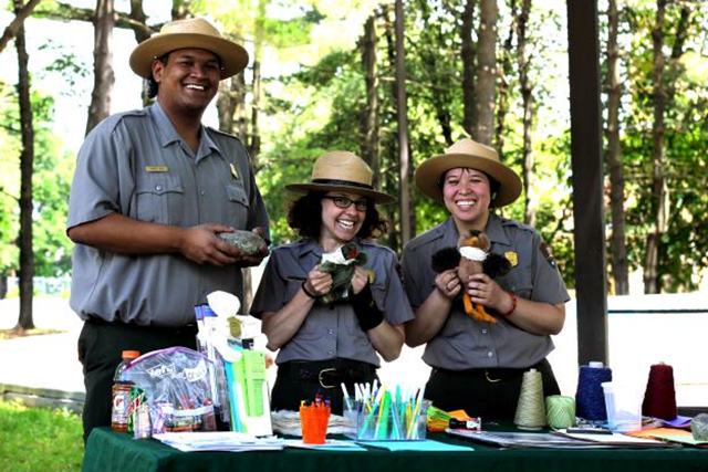 Two female park rangers and one male ranger standing a table holding two puppets and rock waiting to make crafts with kids