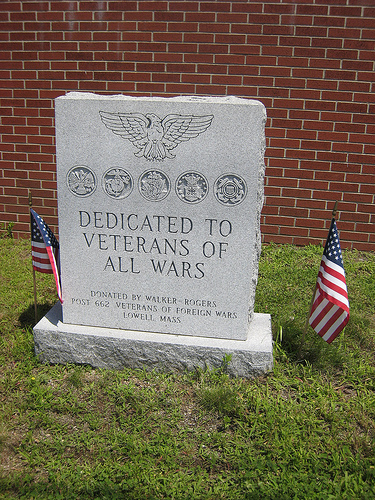"Gray, granite monument with an American Flag on each side. Inscription: ""Dedicated to Veterans of All Wars."""