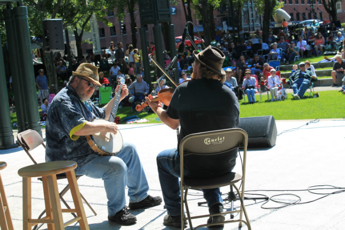 Two men, one with his back to us, the other sits to his left, facing him, play musical instruments, while a crowd in the background watches.