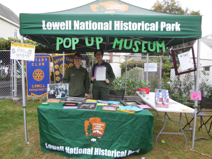 "Two park rangers staff a green tent.  Lowell National Historical Park appear on the top of the canopy and the words ""Pop-up Museum"" appear below.  A table has the National Park Service arrowhead logo on it with brochures on the table."