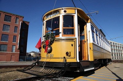 A bright yellow trolley car #4131 is center image.  ON the front is a green wreath with a red ribbon in the center of the front of the trolley, below the windshield.