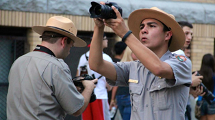 A park ranger holding a camera taking a picture while another park ranger takes a picture with his back towards us.