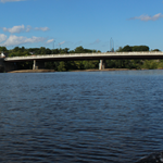 A picture of the Merrimack River with a bridge in the distance