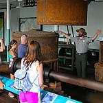 Visitors on tour with a Ranger gesturing to describe the size of a water turbine