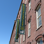 A brick building with a green banner that reads Wannalancit Mill