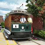 Two men drive a yellow and green trolley car on rail road tracks through downtown Lowell