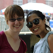Two women wearing sunglasses and summer clothing pose for a picture