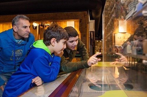 A park ranger helps a father and son explore a model of the factory