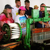 A group of men, women, and children looking at a machine that makes cloth