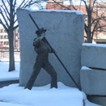 A statue of an Irish man in overalls covered in snow