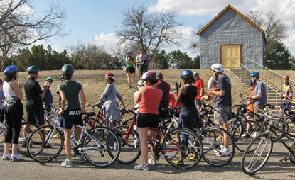 Luci Johnson speaks to cyclists outside the Junction School on the LBJ Ranch.
