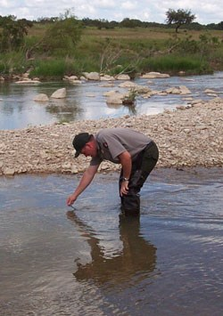 A park ranger conducts tests of the Pedernales River