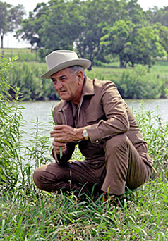 Lyndon Johnson kneeling on the banks of the Pedernales River