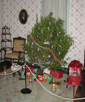 Old-fashioned Cedar Christmas Tree and presents in the parlor of the Boyhood Home.