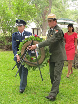 A military representative and park superintendent Russ Whitlock place a wreath at the president's grave.