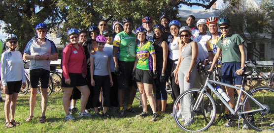 Luci Johnson stands with a group of cyclists in front of the Texas White House.