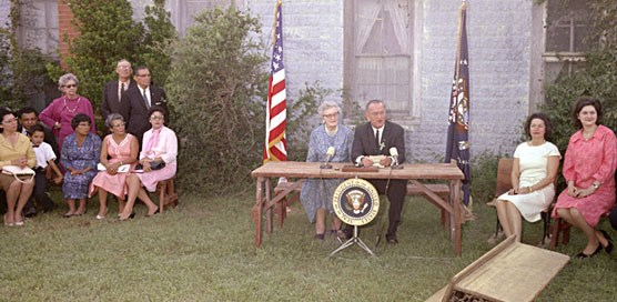 President Lyndon B. Johnson addresses crowd while Lady Bird Johnson and Lynda Bird Johnson listen. Seated next to the President is Kate Deadrich Loney.