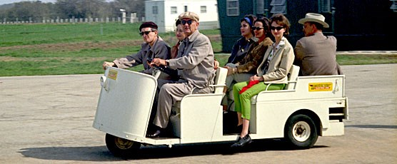 President and Lady Bird Johnson show guests the LBJ Ranch in a golf cart (1964)