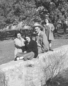 The Johnsons sit on the rock wall surrounding the family cemetery on the LBJ Ranch