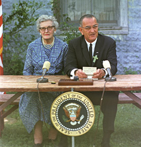 President Johnson sits besides Ms. Kate Deadrich Loney at the signing of the Elementary and Secondary Education Act.