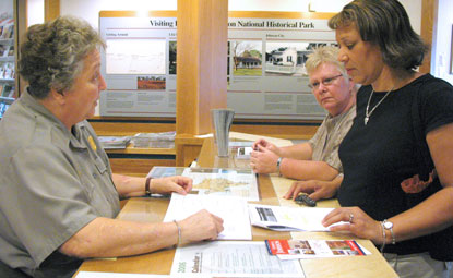 Park ranger assisting visitor at information desk