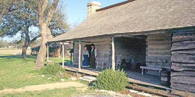 Volunteers in 1860s clothing stand on the porch of the Johnson Settlement cabin