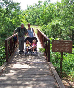 A family crosses the bridge to the Johnson Settlement
