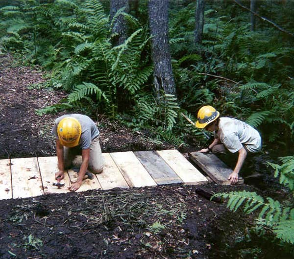 Two volunteers repairing a footbridge in the park