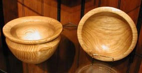 Two highly polished wooden bowls sit next to each other, one tipped so you can see the grain of the wood on its inside, the other flat on the glass surface.
