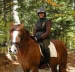 A smiling park volunteer sits astride a brown horse.