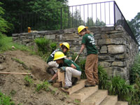 Student volunteers in bright yellow helmets and dark green t-shirts construct a wooden stair next to a stone terrace.