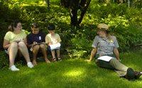 Three children and a park ranger sit in the shady grass and work on Junior Ranger actitivies.