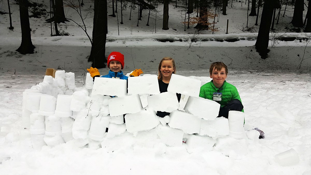 blocks of snow piled up with kids behind them