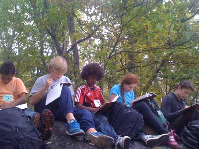 students journaling on rock