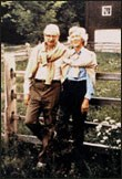 This color photograph shows Laurance Rockefeller on the left and his wife Mary on the right, standing in front of a split rail wooden fence and a barn, with white flowers peeking through the rails. They both have sweaters tied around their necks.
