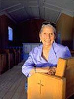 A smiling silver-haired woman in a lavender-colored blouse leans on a wooden altar inside the cool dark of the small chapel.