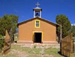 A pinkish-brown adobe chapel stands against the deep blue New Mexican sky.