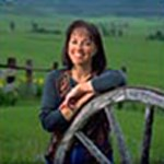A dark-haired woman in a blue shirt leans against an old wooden wagon wheel, with green pastures behind her.