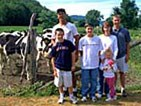 A family of six stands in front of a wooden fence, with black and white Holstein cows grazing behind them.
